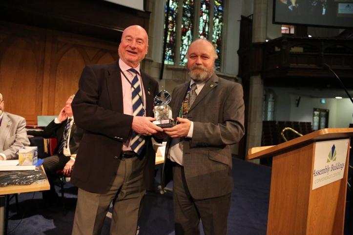 Ian Mackenzie receives the award from Godwin Stewart, National Communications Officer.
